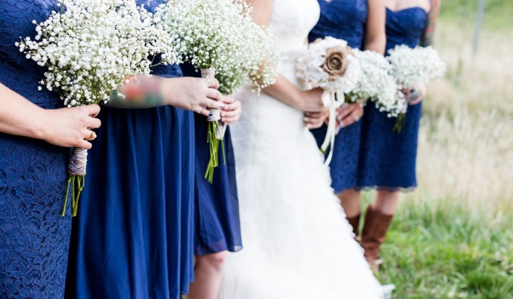 bride with her bridesmaids holding their white bouquets