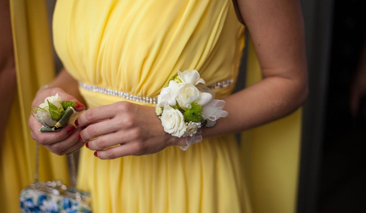 bridesmaid wearing a yellow dress with a white flower corsage