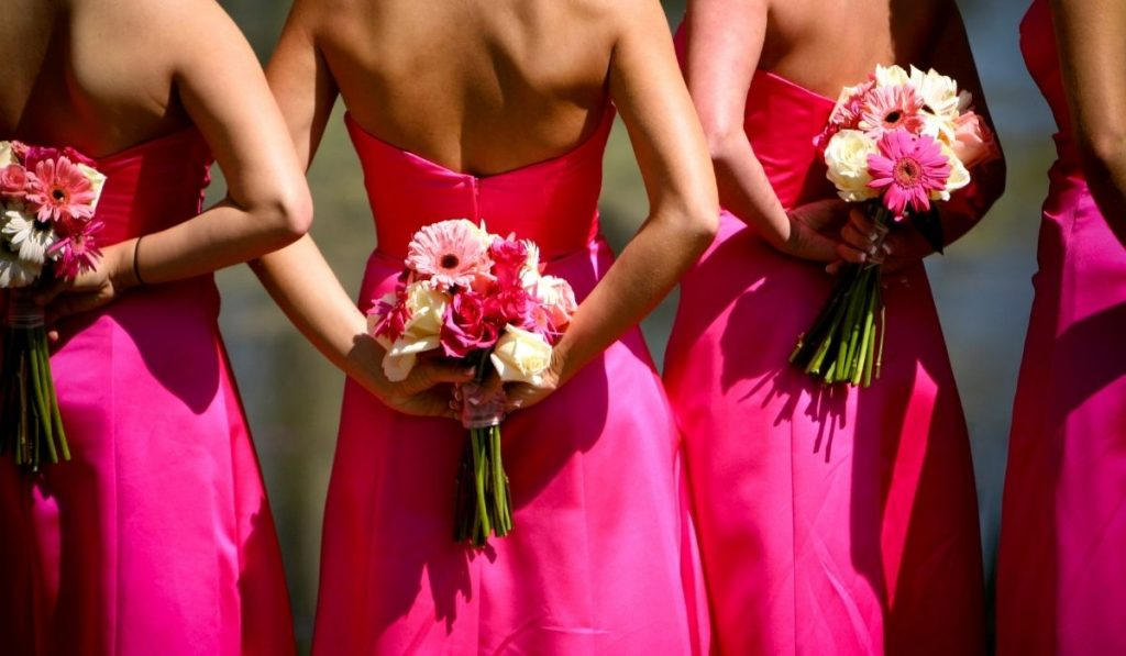 bridesmaids wearing bright pink dresses with their bouquets at their back for picture taking