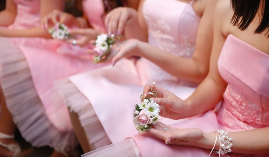 bridesmaids wearing pink dresses and holding their corsage