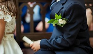wedding usher with a white rose corsage