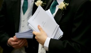 wedding ushers holding the order of service booklets