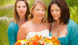 bride holding orange bouquet flowers and her bridesmaids wearing teal dresses
