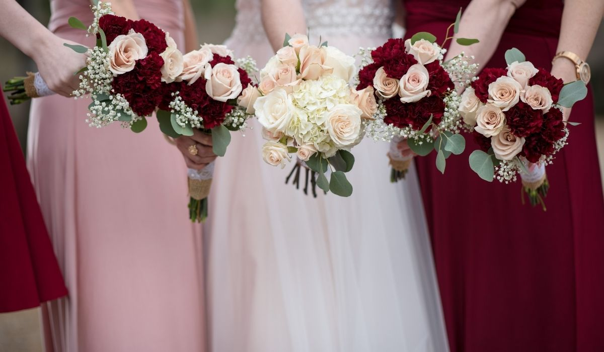 woman holding a Burgundy and Dusty Rose flowers in a wedding