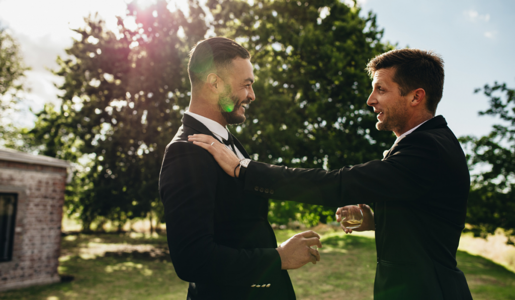 Groom talking with his best man with drinks in hand during a party