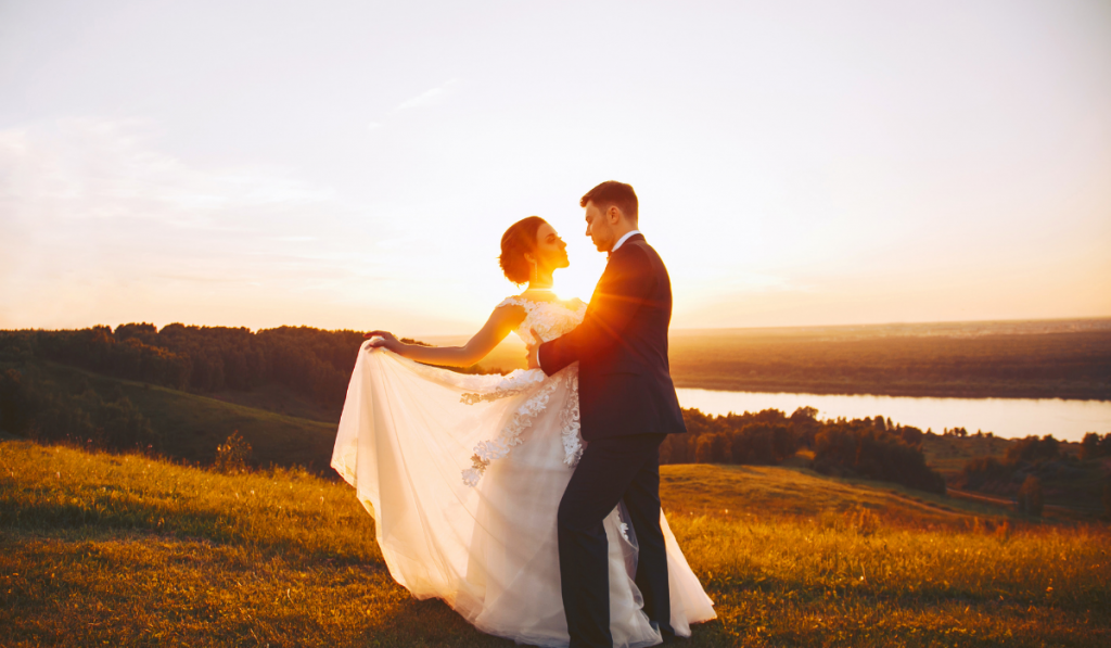 Bride and groom embracing with sunset background