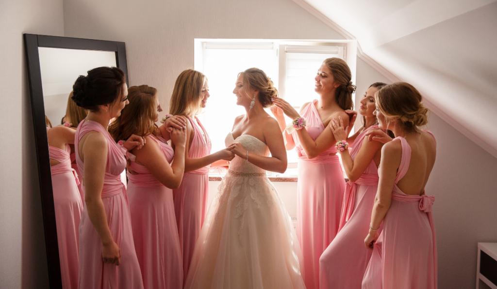 Bride with bridesmaid posing in hotel or fitting room at wedding day