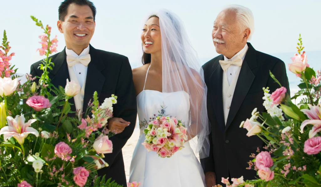 Happy Bride and father looking at groom with flowers on foreground