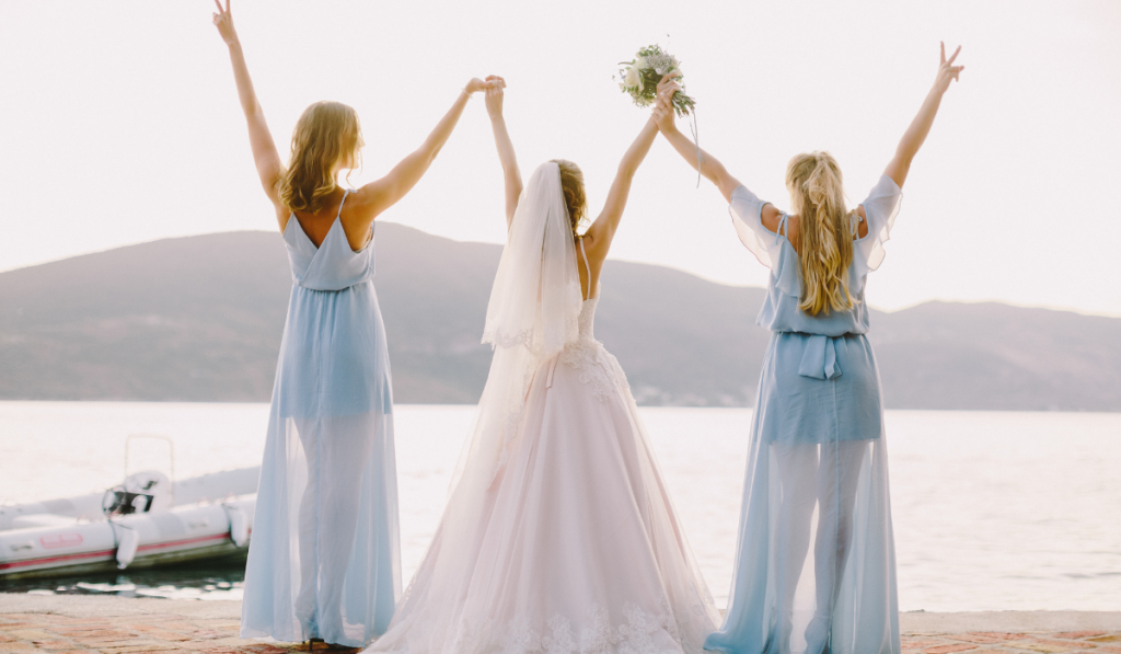Two maid of honors wearing a blue gown and the  bride in the center wearing white gown facing the sea