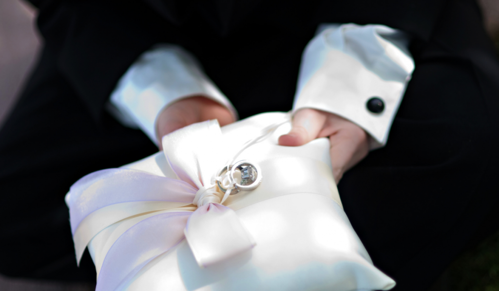 A ring bearer hold the rings on a silk pillow
