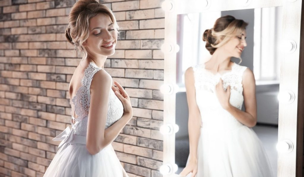 bride in her wedding gown in front of the mirror