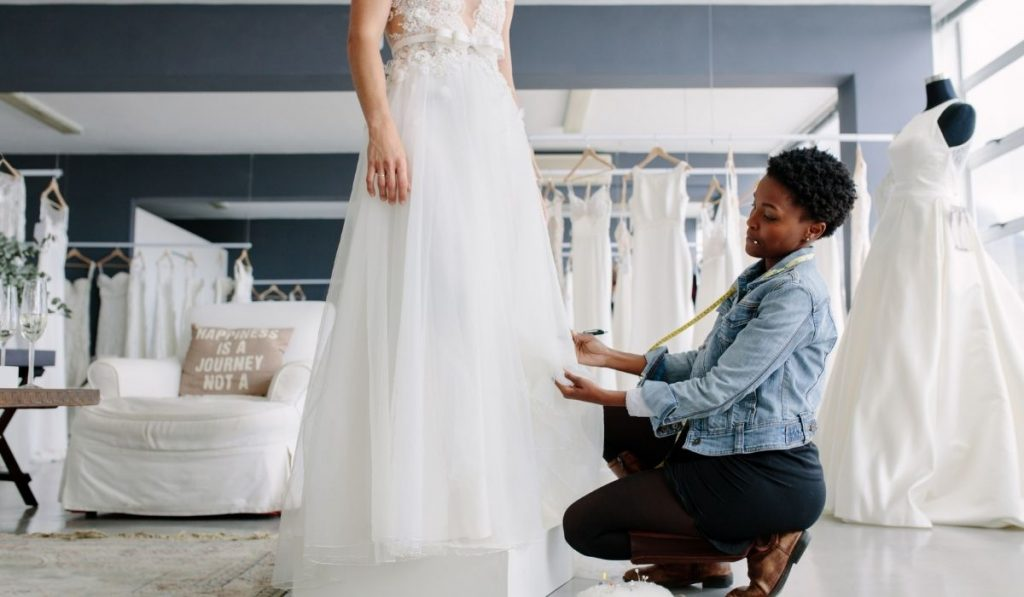 woman helping the bride with some adjustments on her wedding gown