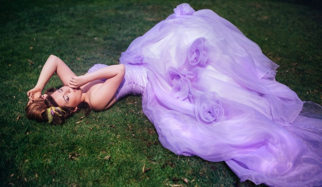 woman in purple gown lying on the grass