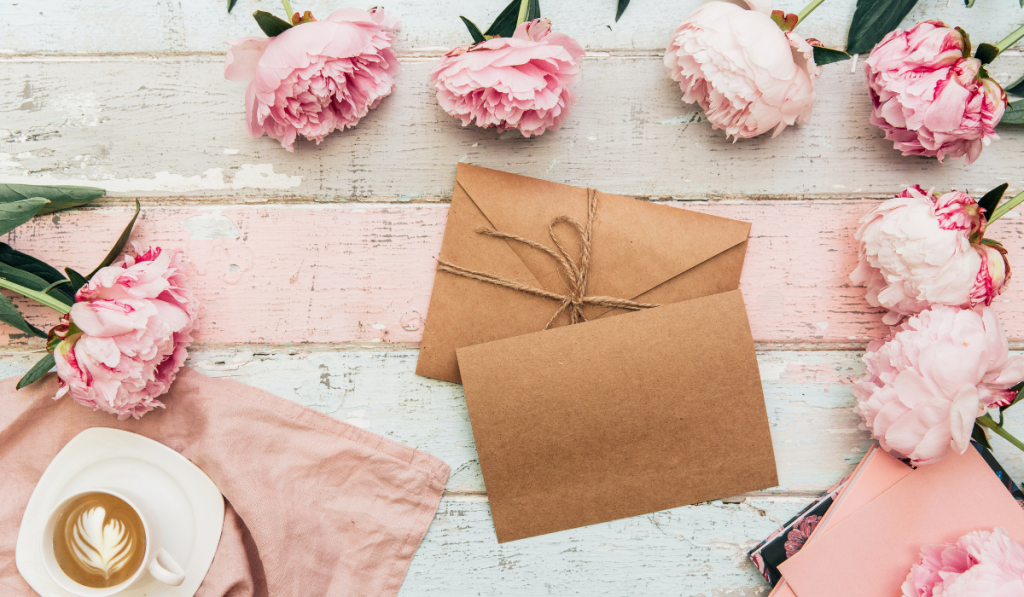 Beautiful pink flowers and card with envelope on vintage background.