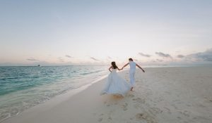 newly weds running by the seashore