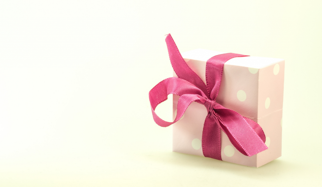 A cute gift wrapped with pink polka dots wrapper.