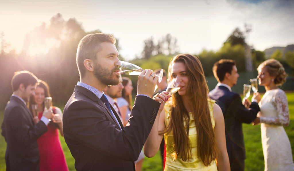 A girl and boy drinking champagne with the bride and groom in the background.