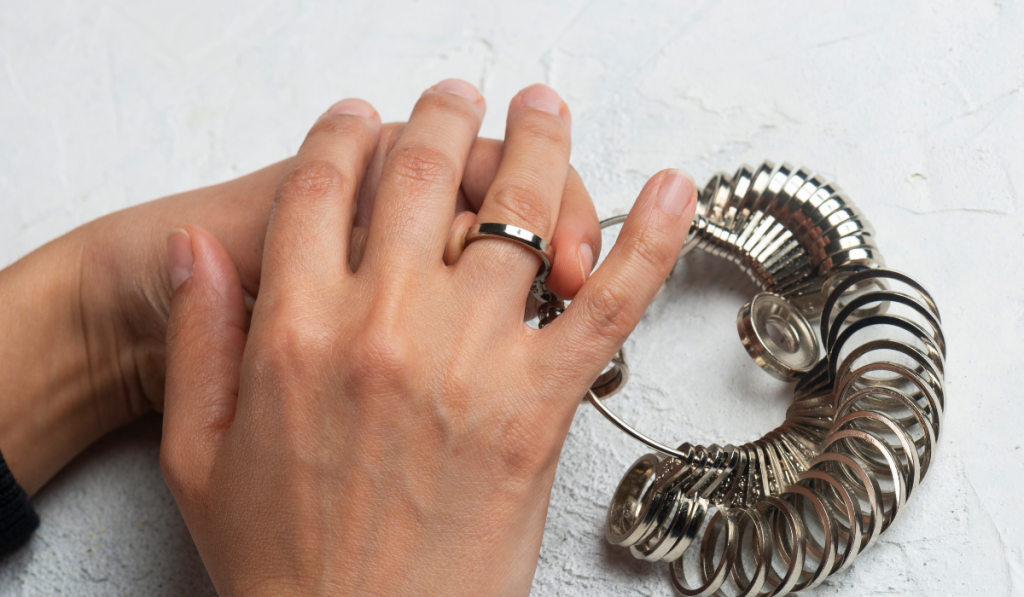 Woman trying the ring sizer on white background.