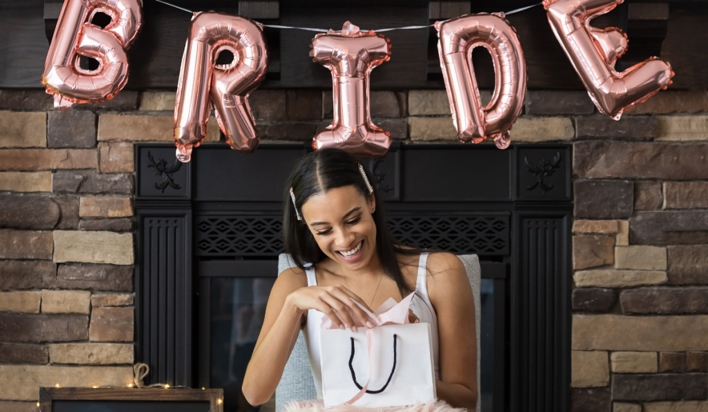 A girl waring white sitting at the center with pink balloons above that spells bride.