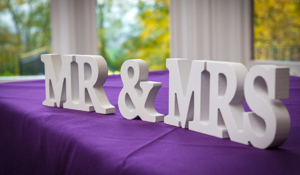 Wooden Mr. and Mrs. on a violet mantel